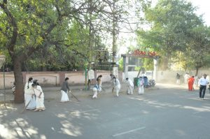 Students and teachers cleaning patches of Kalawad road.