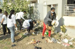 Girl students cleaning up the neighborhood on a Sunday.